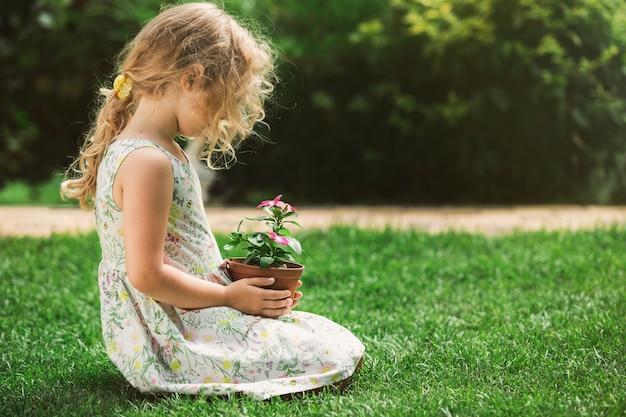 Menina loira segurando uma planta de flor jovem nas mãos sobre fundo verde