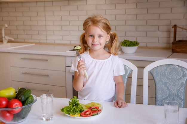 Menina loira sentada à mesa na cozinha comendo legumes