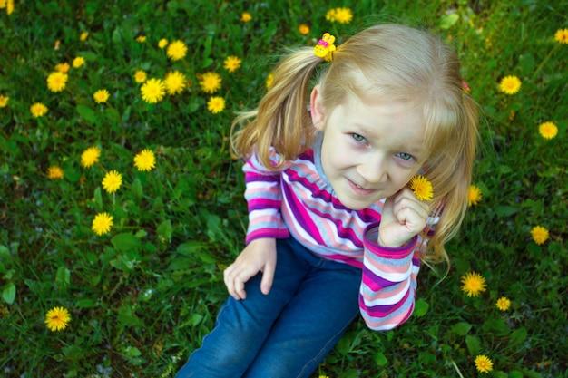 Menina loira sentada na grama ao ar livre