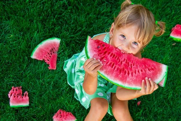 Menina loira sentada na grama e comendo uma fatia de melancia no verão.
