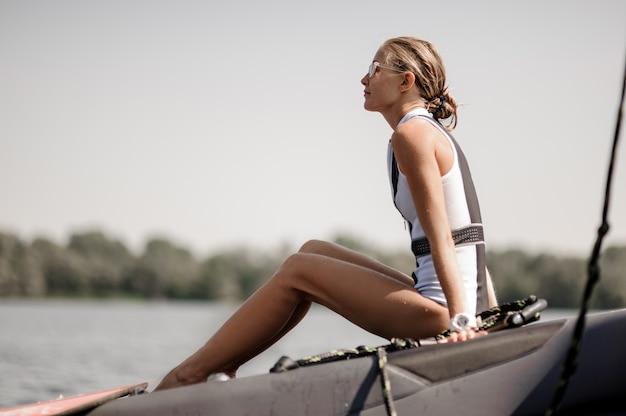 Menina loira sentada perto do lago no cais