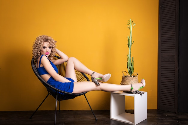 Menina loira, sentado em uma cadeira com um cacto