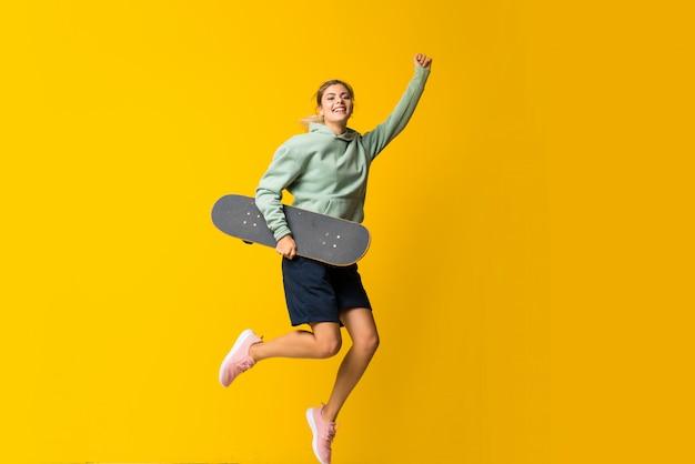 Menina loira skatista adolescente saltando sobre amarelo isolado