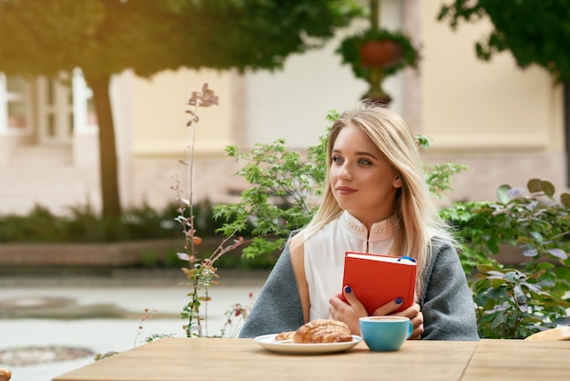 Menina loira sonhadora, mantendo o livro vermelho, sentado ao ar livre.