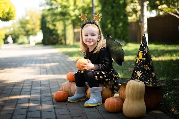 Menina loira sorridente alegre fantasiada de bruxa de carnaval sentada em abóboras no dia das bruxas ao ar livre