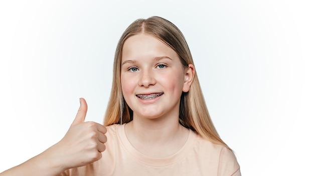 Menina loira sorridente com aparelho ortodôntico segurando o polegar para cima tratamento ortodôntico de dentes desalinhados ou tortos