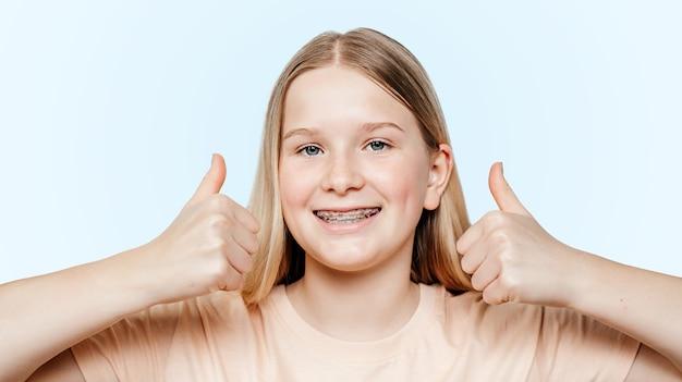 Menina loira sorridente com aparelho ortodôntico segurando o polegar para cima, tratamento ortodôntico