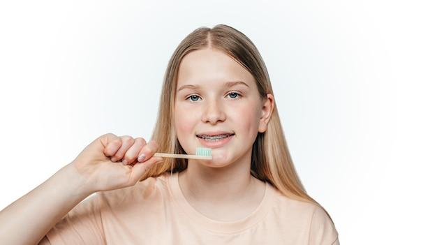 Menina loira sorridente com aparelho ortodôntico segurando uma escova de dentes de bambu ecológica