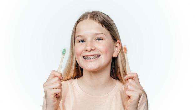 Menina loira sorridente com aparelho ortodôntico segurando zero desperdício de escova de dentes de bambu