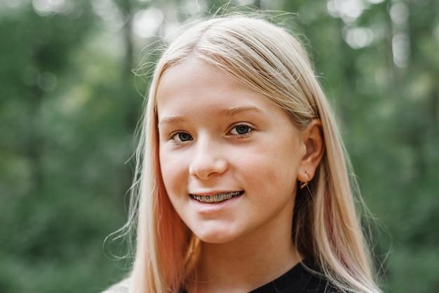 Menina loira sorridente com aparelho ortodôntico