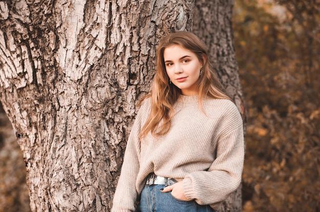 Menina loira sorridente com roupas casuais posando ao ar livre