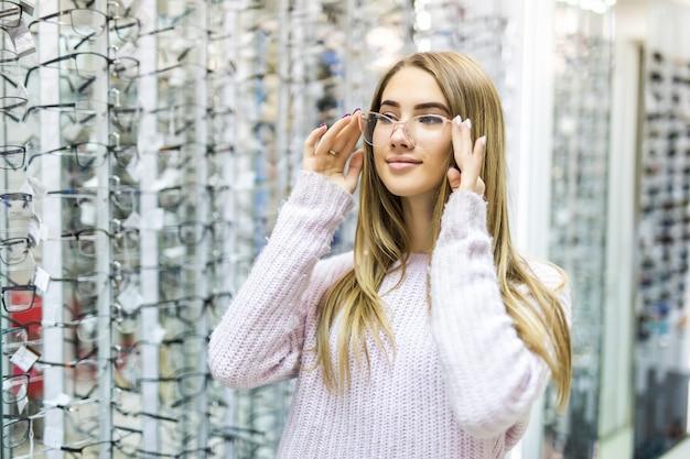 Menina loira sorridente com suéter branco escolhe novos óculos médicos em loja profissional