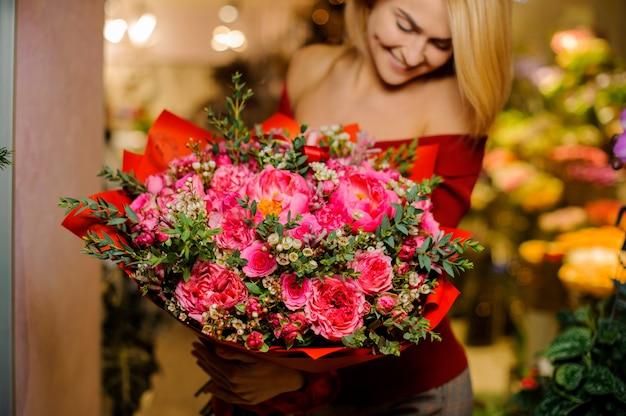 Menina loira sorridente com um buquê grande e brilhante de flores para o dia dos namorados