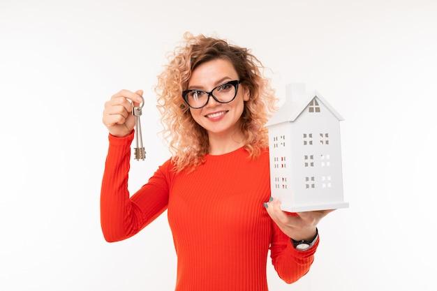 Menina loira sorridente com um layout de casa e chaves em branco