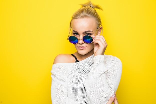 Menina loira sorridente com um suéter branco moderno e óculos de sol azuis brilhantes posando em amarelo
