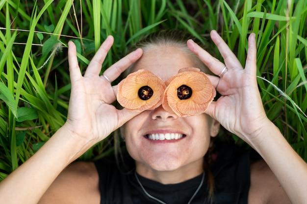 Menina loira sorridente com uma flor acima de cada olho
