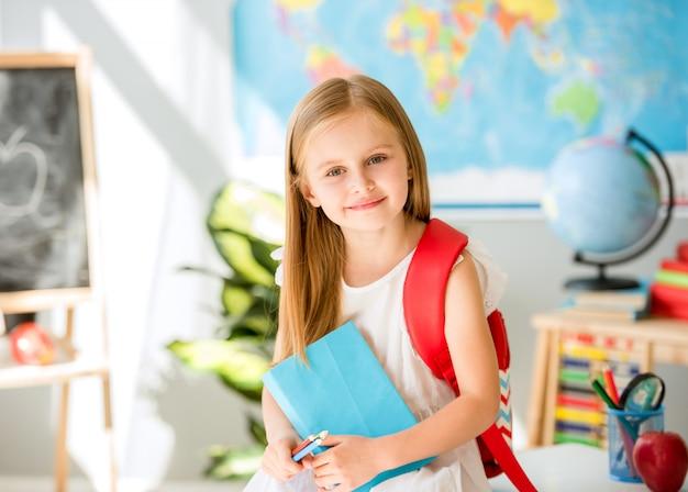 Menina loira sorridente em pé na sala de aula da escola