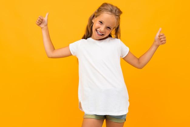 Menina loira sorridente em uma camiseta branca com uma maquete