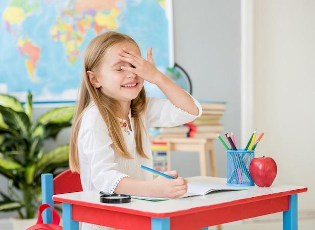 Menina loira sorridente fez um mistke escrevendo na sala de aula da escola