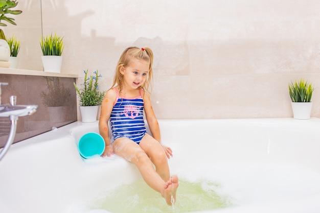 Menina loira sorridente no maiô azul, espirrando em um grande banheiro moderno com espuma. . higiene infantil. shampoo, tratamento capilar e sabonete para crianças.