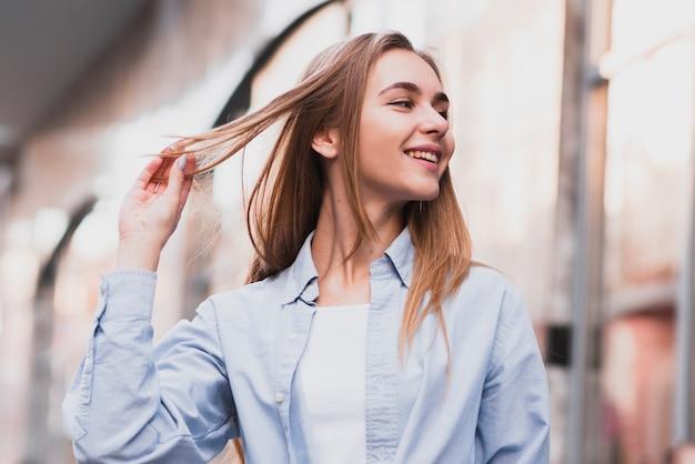 Menina loira sorridente, organizando o cabelo dela