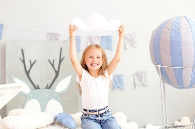 Menina loira sorridente segurando um travesseiro de nuvem de um balão decorativo. a criança brinca no quarto das crianças com brinquedos. o conceito de infância, viajar. criança no jardim de infância
