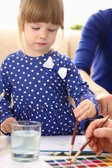 Menina loira sorridente segurando uma escova no braço