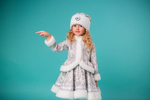 Menina loira sorrindo em traje de donzela de neve isolar na parede azul