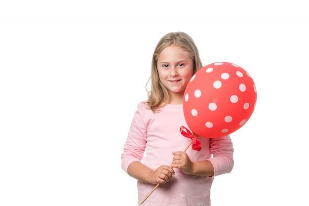 Menina loira sorrindo para a câmera com um balão