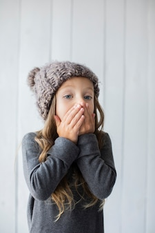 Menina loira surpresa com chapéu de inverno
