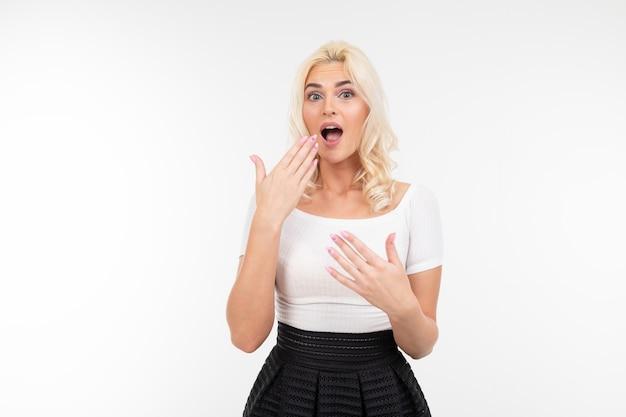 Menina loira surpresa em uma camiseta branca sobre um fundo branco com espaço de cópia