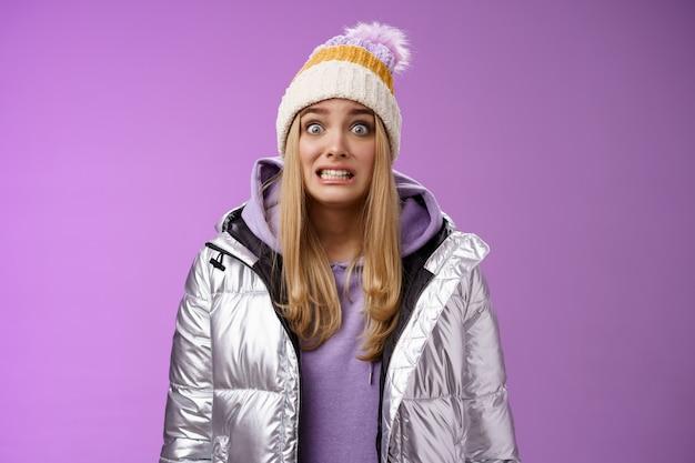 Menina loira tímida fofa preocupada desajeitada em jaqueta prateada com capuz chapéu de inverno cerrar os dentes olhos arregalados, câmera ooops, cometer o erro de pé nervoso que alguém observe, fundo roxo copie o espaço