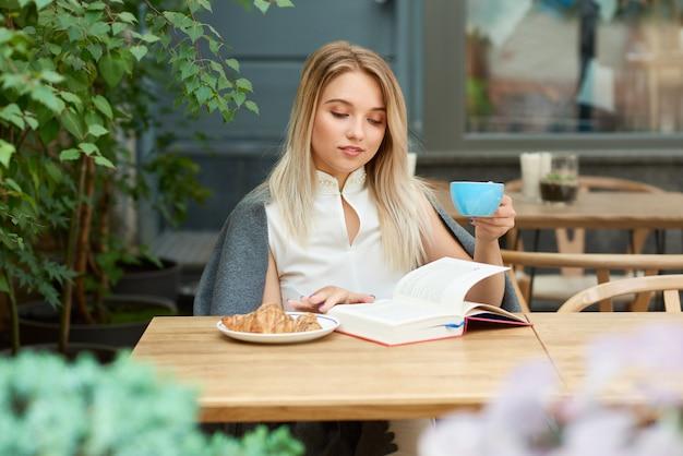 Menina loira tomando café enquanto lê um livro sentado no salão do café.