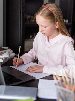 Menina loira tomando notas na aula on-line