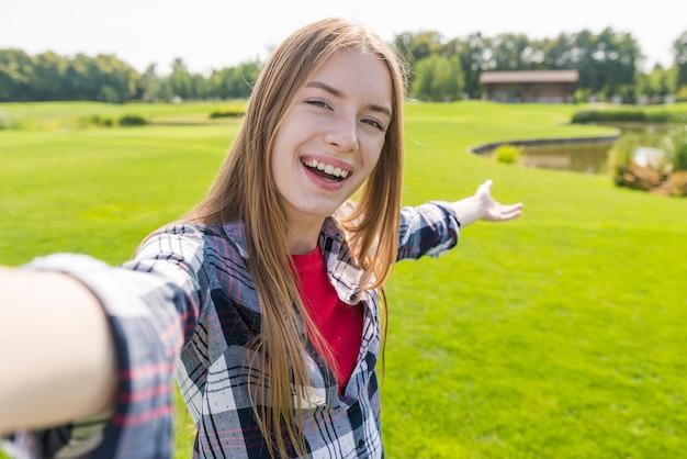 Menina loira tomando uma selfie com um belo fundo