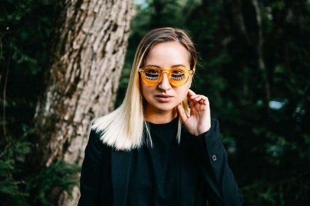 Menina loira, vestida de jaqueta preta com óculos amarelos com cílios postiços