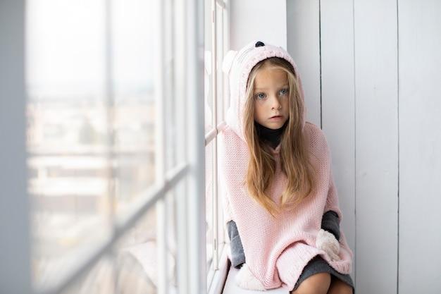 Menina loira, vestindo blusa rosa