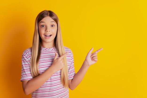 Menina louca e chocada com o dedo indicador do espaço vazio sugerir escolha sobre fundo amarelo