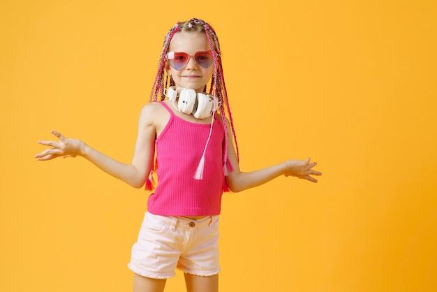 Menina louca expressiva dj na moda com roupas brilhantes, fones de ouvido e