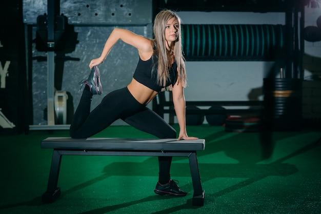 Menina loura bonita da aptidão nova muscular que levanta uma cruz do peso cabida no gym.