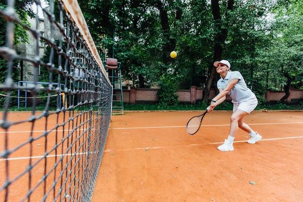 Menina loura bonita nova no uniforme com a raquete de tênis no ombro que está na corte de tênis exterior moderna no por do sol.