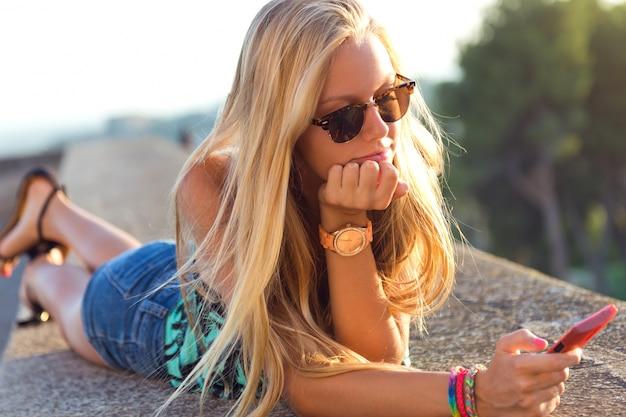 Menina loura bonita que senta-se no telhado com telefone móvel.