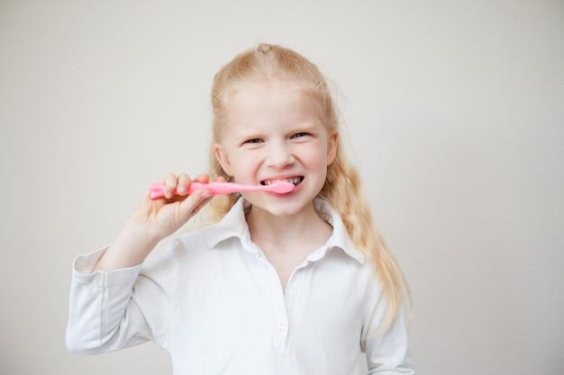 Menina loura bonito nova com os dentes da limpeza da escova de dentes.