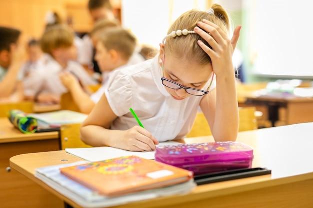 Menina loura com os vidros grandes que sentam-se na sala de aula, studing, sorrindo. educação na escola primária, primeiro dia na escola