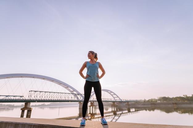 Menina loura desportiva bonita forte segura que está no molhe perto do rio após o treinamento do amanhecer.