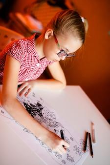 Menina loura no vestido cor-de-rosa e nos vidros pretos grandes que tiram papai noel. tema de ano novo