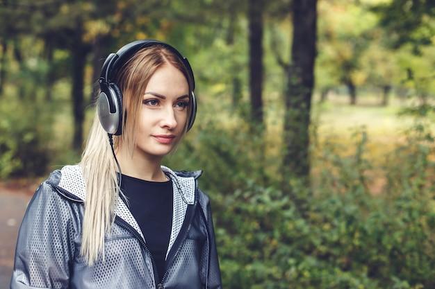 Menina loura nova atrativa que anda no parque, escutando a música em fones de ouvido.