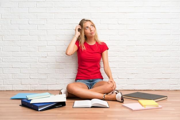 Menina loura nova do estudante com muitos livros no assoalho que tem dúvidas e com confundir a expressão da cara