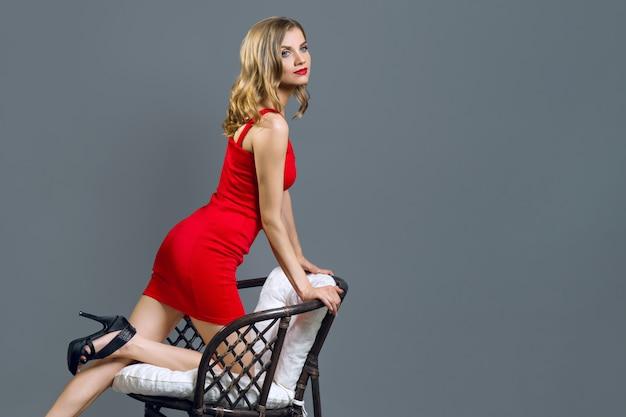 Menina loura nova elegante no vestido vermelho no cinza