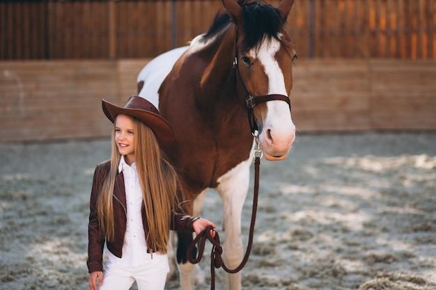Menina loura pequena bonito com cavalo no rancho